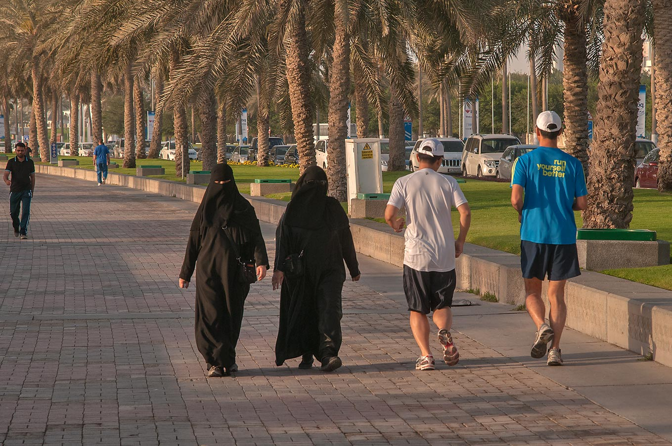 Two couples jogging on Corniche promenade at morning. Doha, Qatar