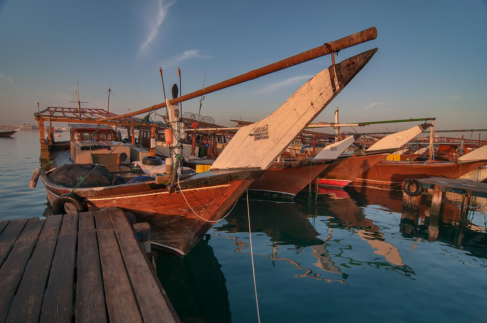 Traditional dhow fishing boats in harbor in Al Wakra at sunrise. Qatar