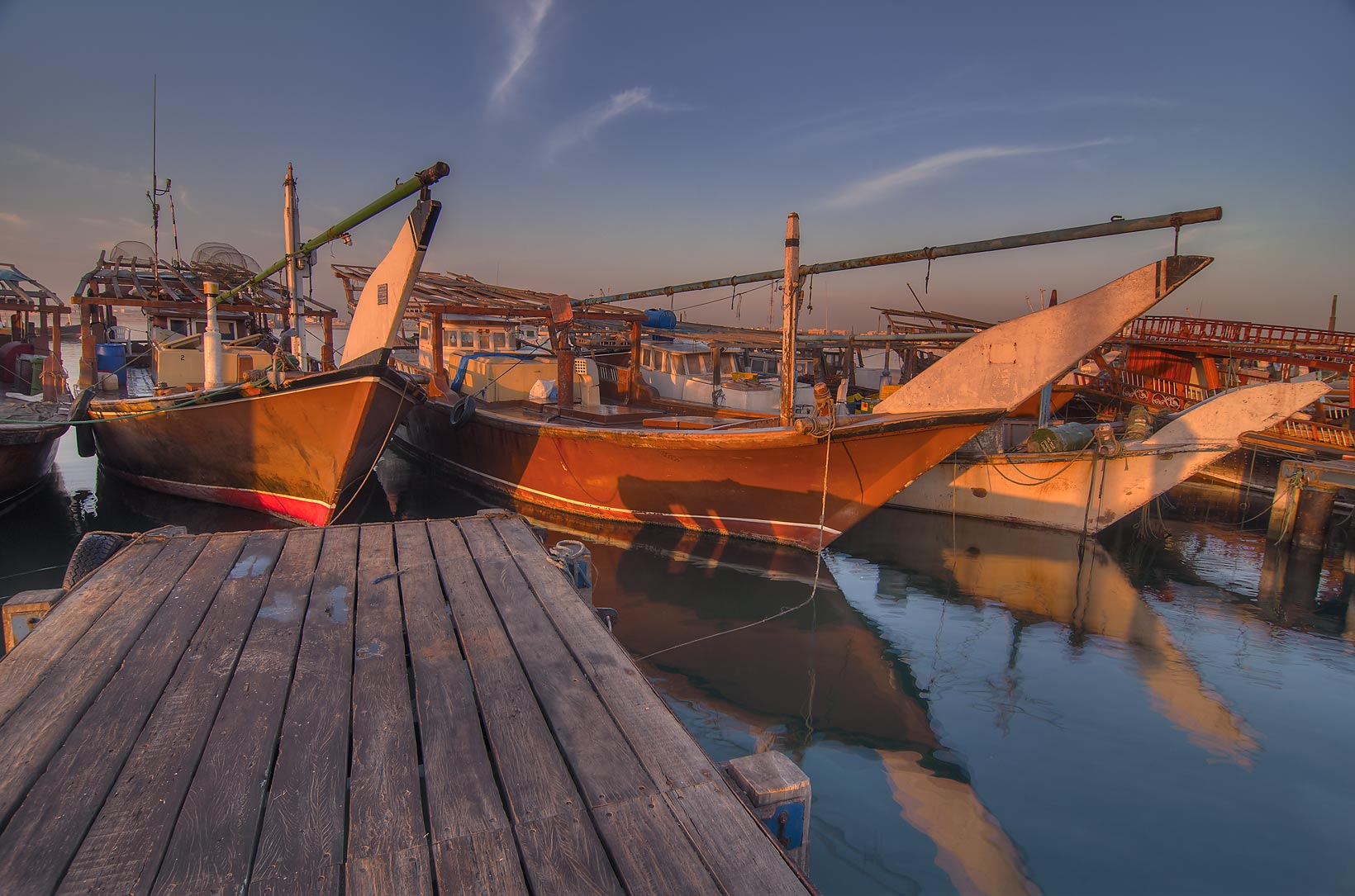 Prows of dhow boats in harbor in Al Wakra at sunrise. Qatar