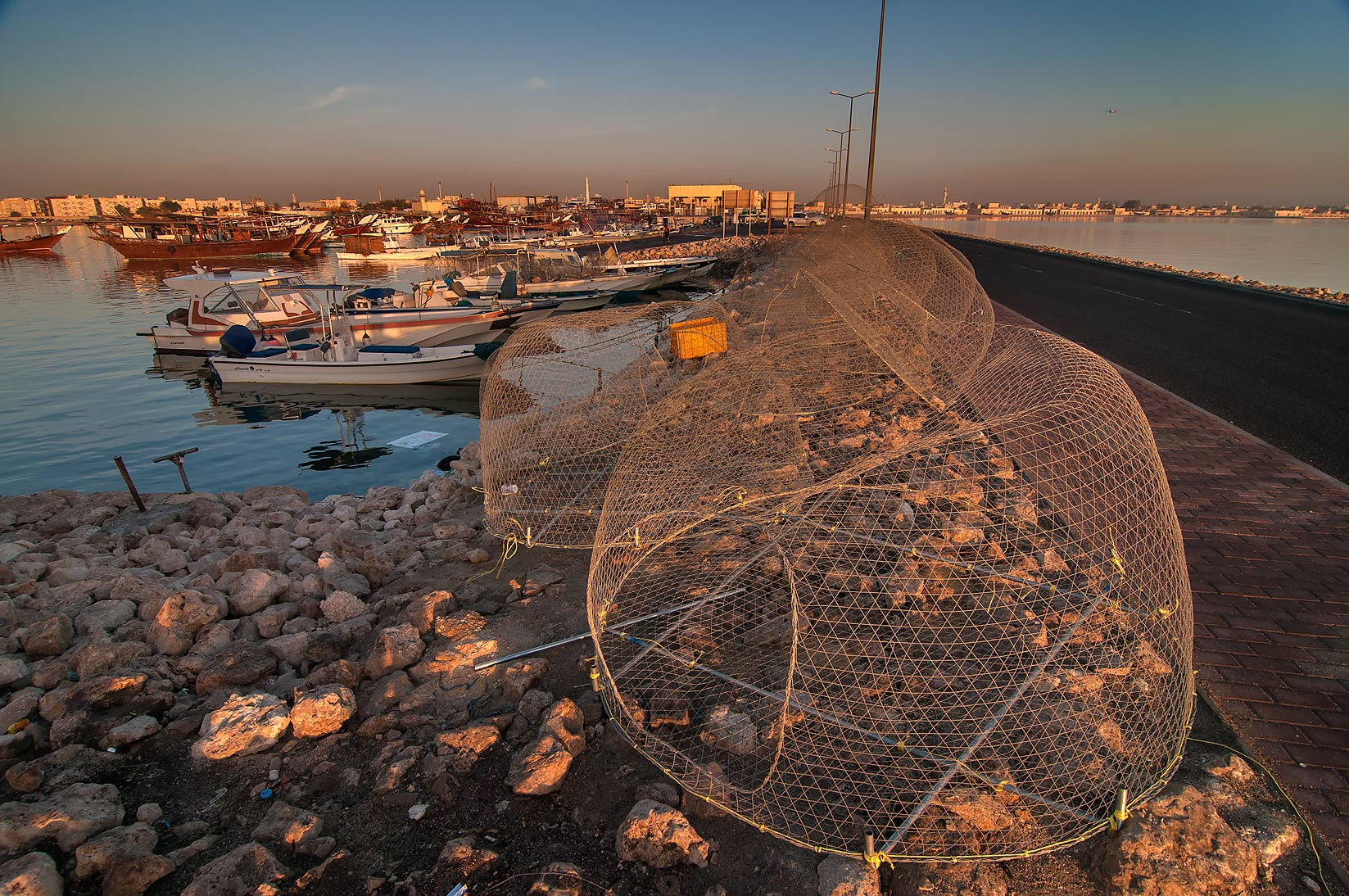 Domed wire fish traps (gargoor) in harbor in Al Wakra at sunrise. Qatar