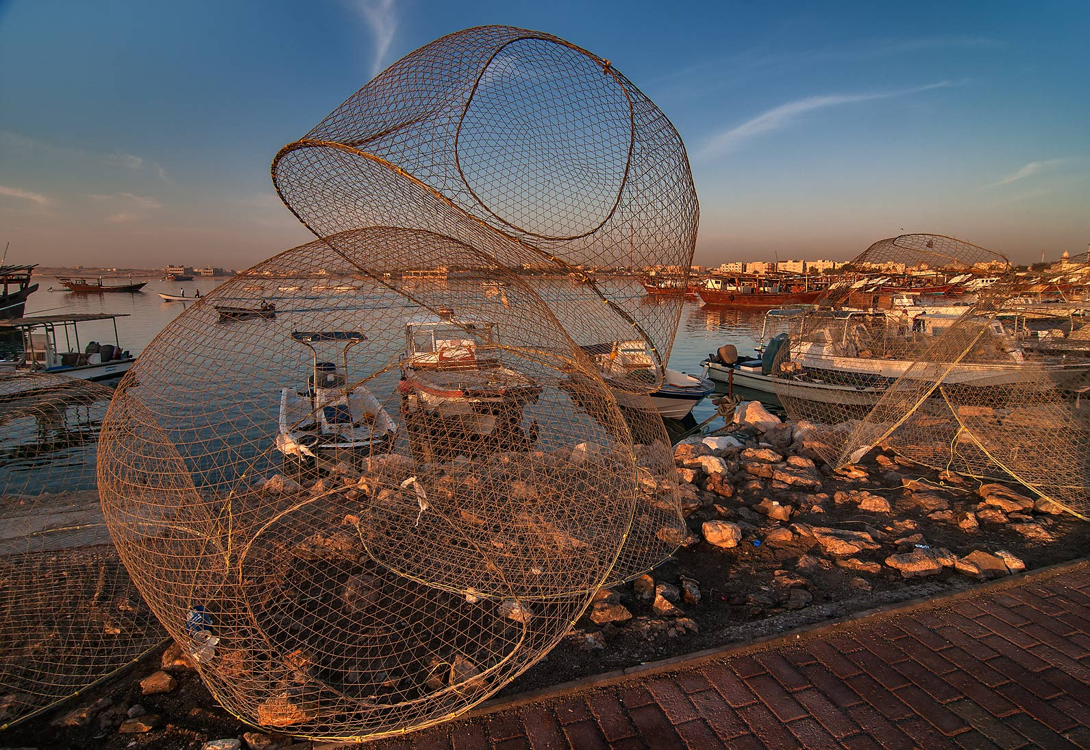 Domed wire fish traps (gargoor) and boats in harbor in Al Wakra at sunrise. Qatar