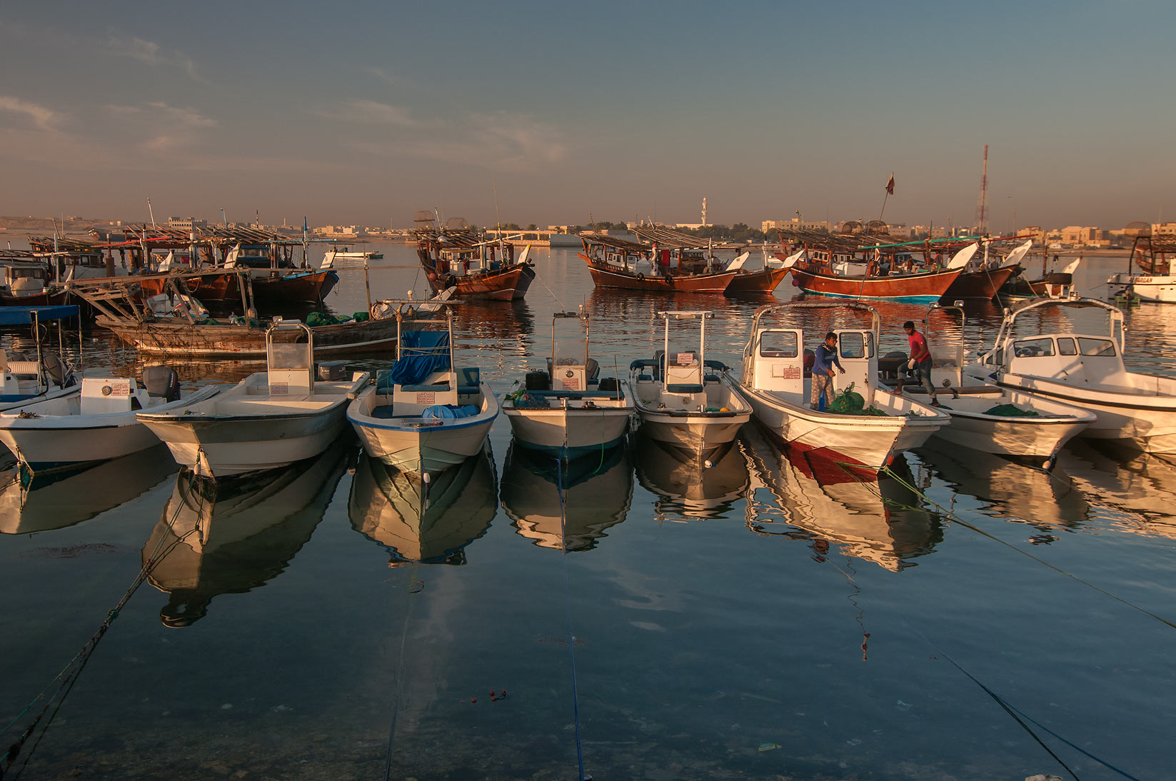 Reflections of fishing boats in harbor in Al Wakra at sunrise. Qatar
