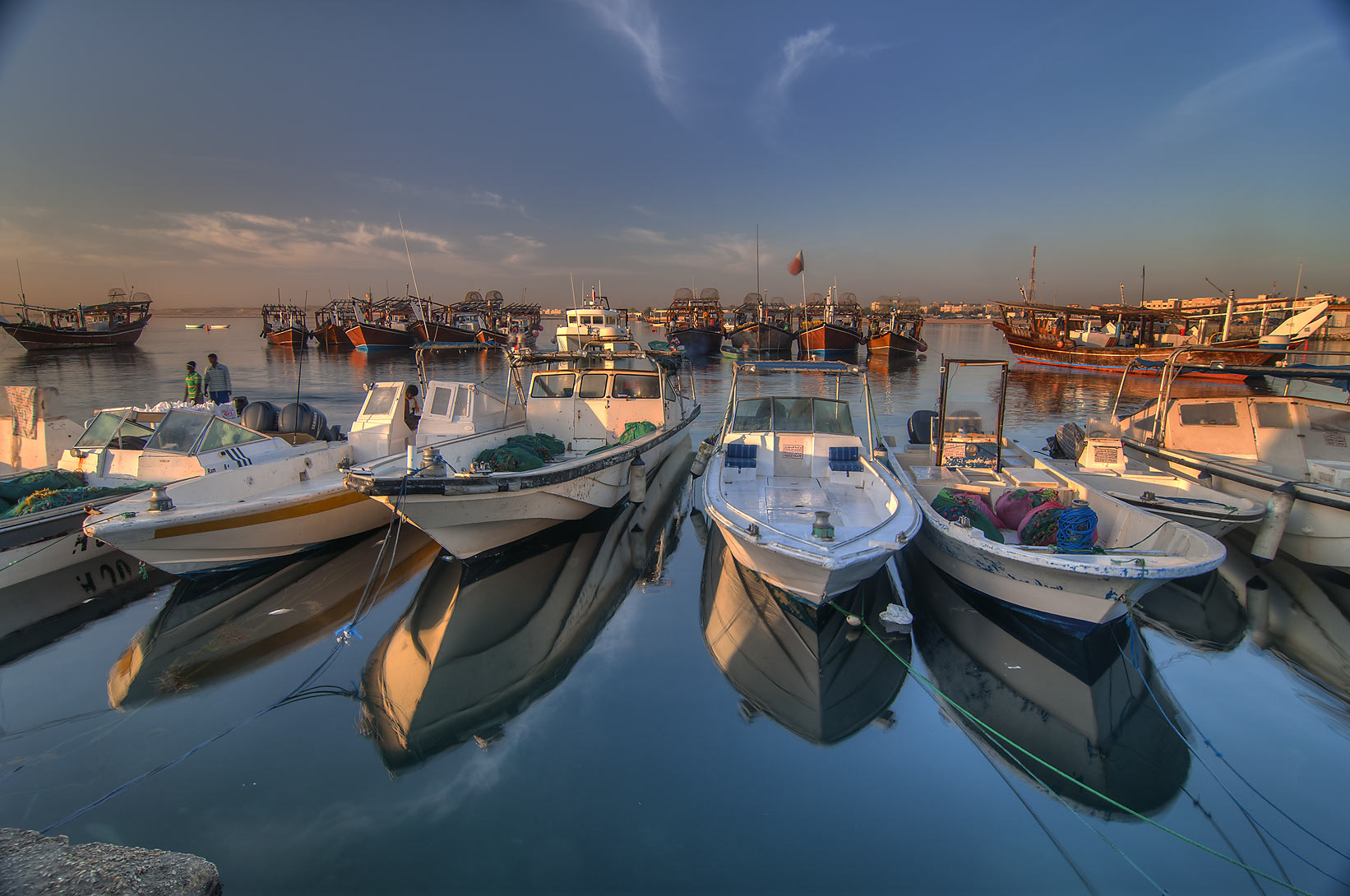 Rows of fishing boats in harbor in Al Wakra at sunrise, view from a pier. Qatar