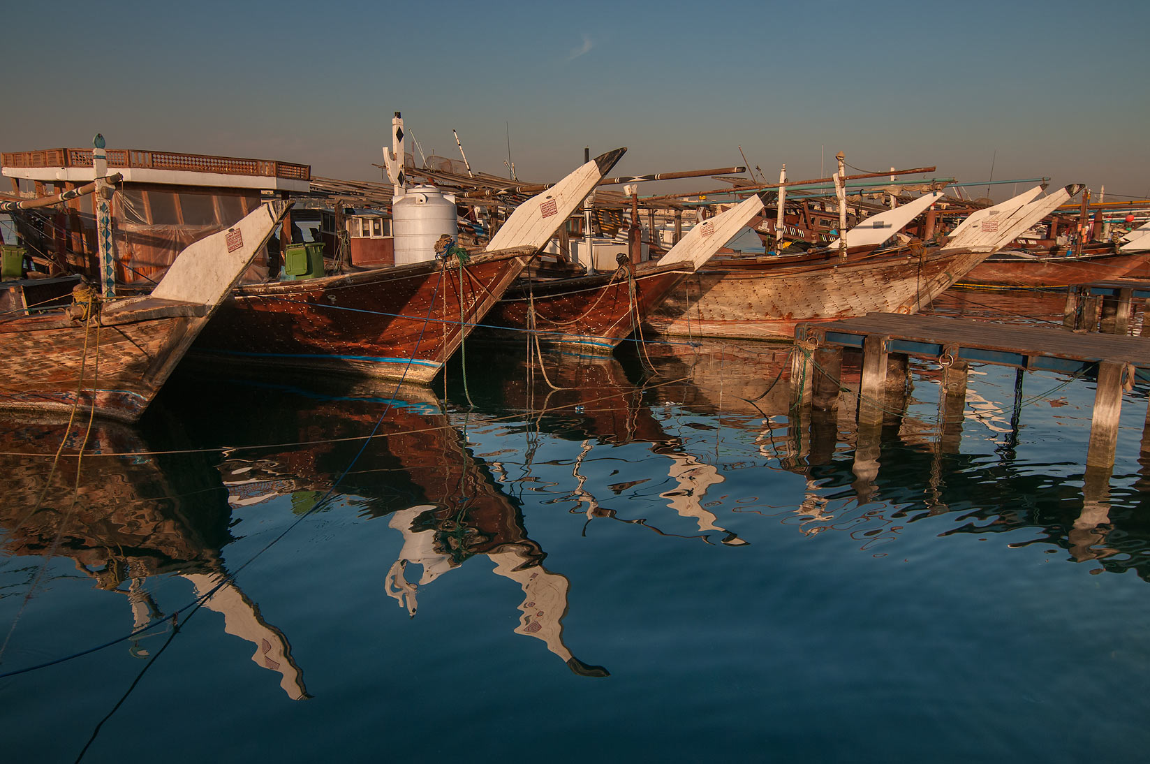 Reflections of prows of dhow fishing boats on a pier in Al Wakra. Qatar
