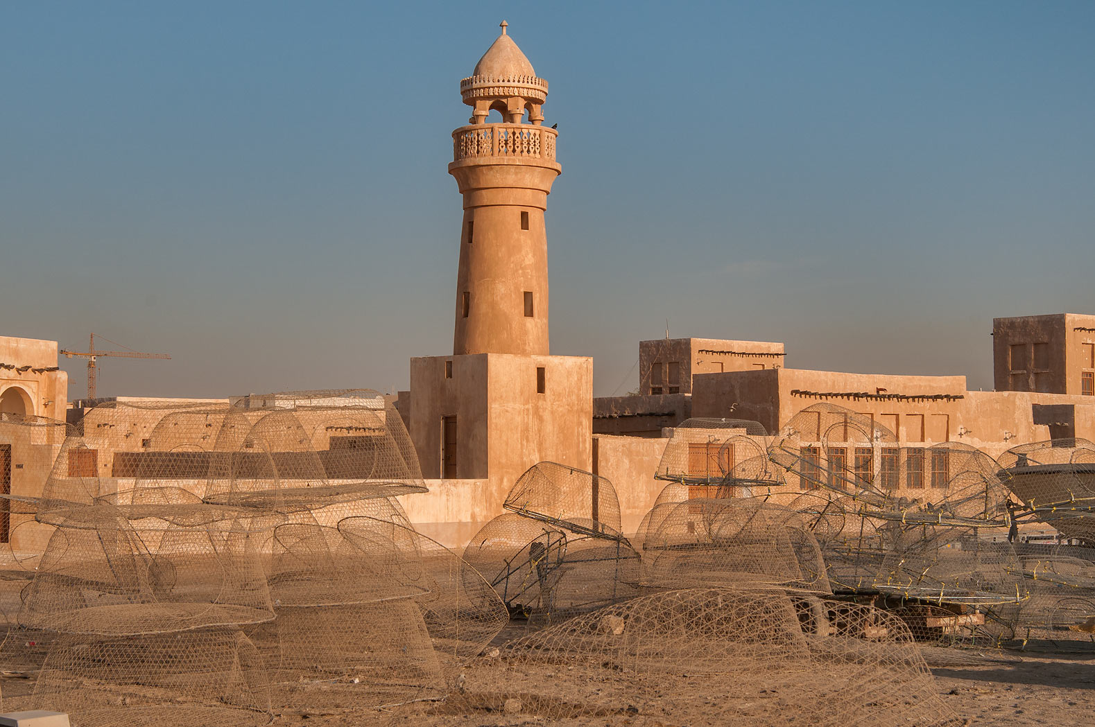Restored mosque near a pier in Al Wakra, with domed wire fish traps in foreground. Qatar