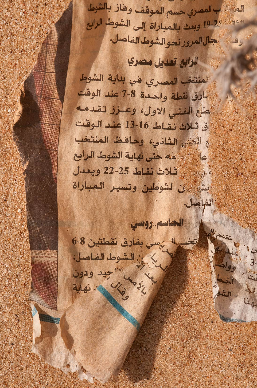 Remains of Arabic newspaper in desert sand in...Mesayeed, south-west from Doha. Qatar