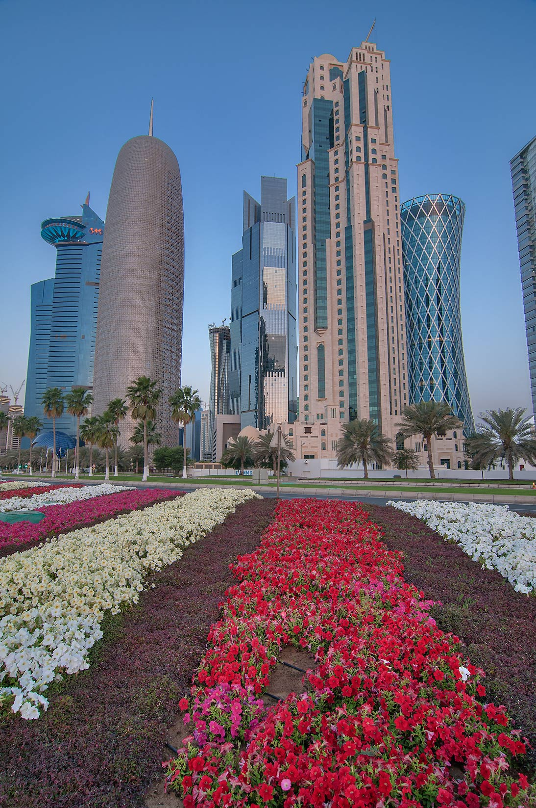 West Bay towers from a flower bed near tea pot...on Corniche promenade. Doha, Qatar