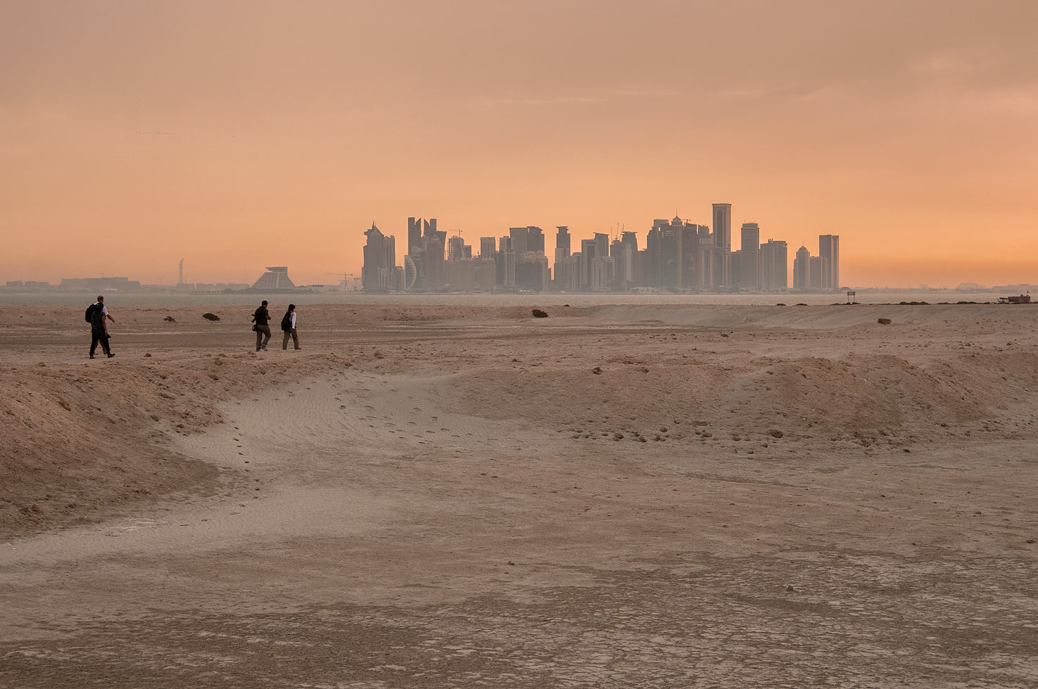 Walking across Safliya Island near Doha at sunset, with West Bay in background. Qatar