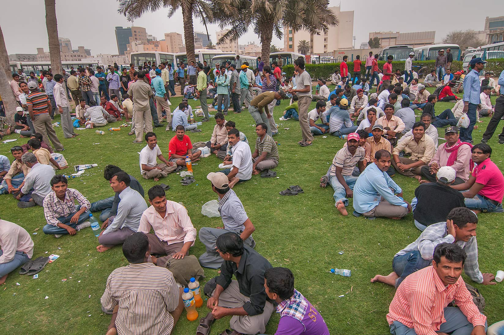 Migrant workers gathering on a lawn near Central Bus Station Al Ghanim. Doha, Qatar