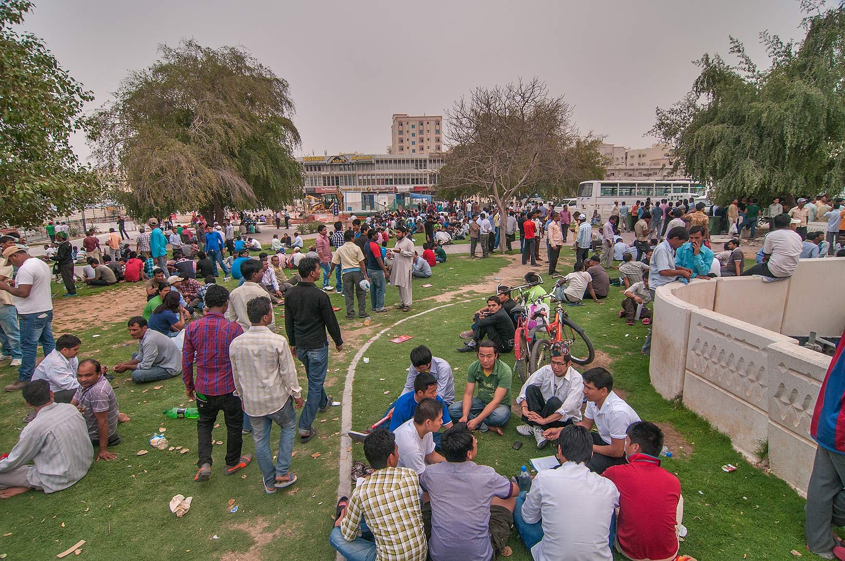 Migrant workers sitting on a lawn near Grand...Al Ghanim on Friday. Doha, Qatar