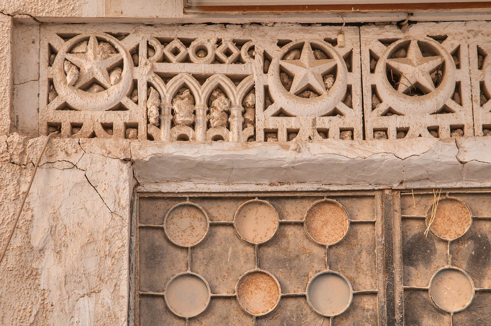 Concrete latticework of ventilation over a door...Al Doha Al Jadeeda area. Doha, Qatar