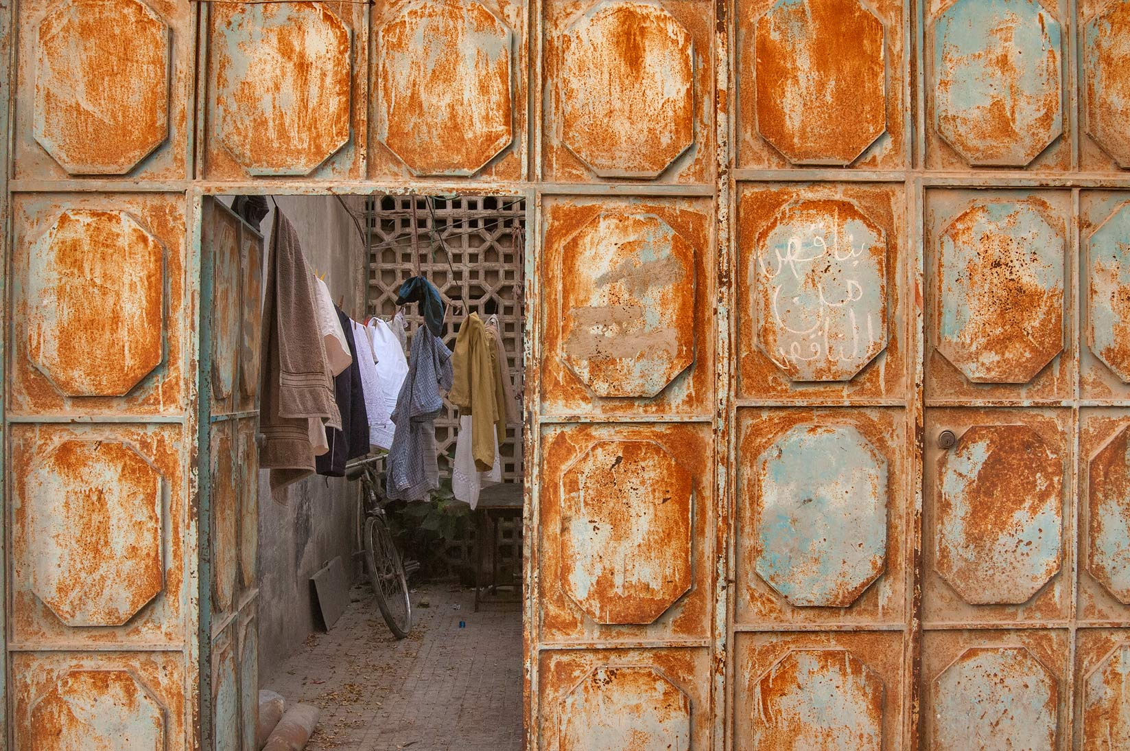 Rusty doorway of a shared apartment at Sikkat Ibn Al Rabei, Najma area. Doha, Qatar