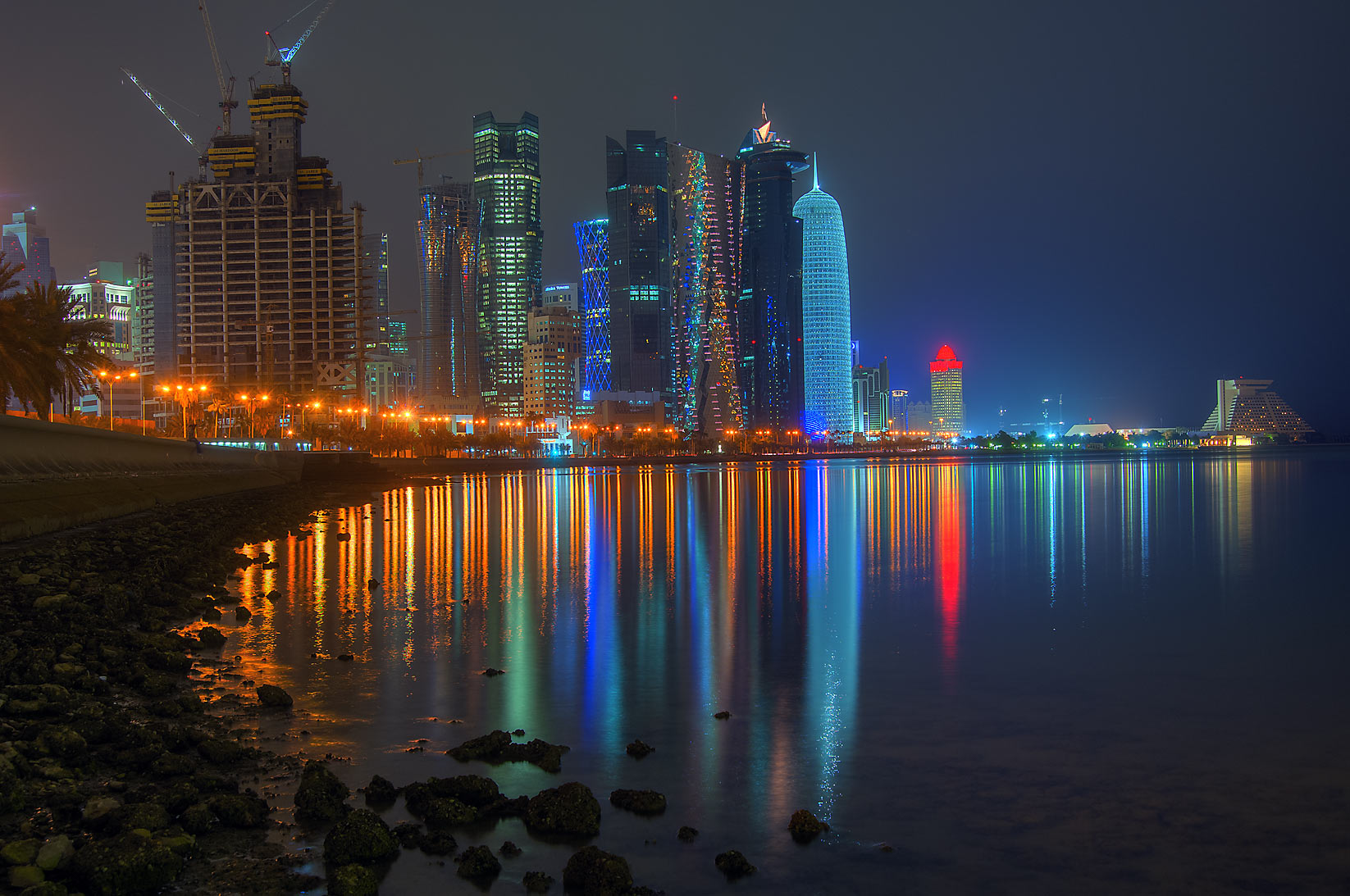 Lights of West Bay from Corniche promenade at low tide. Doha, Qatar