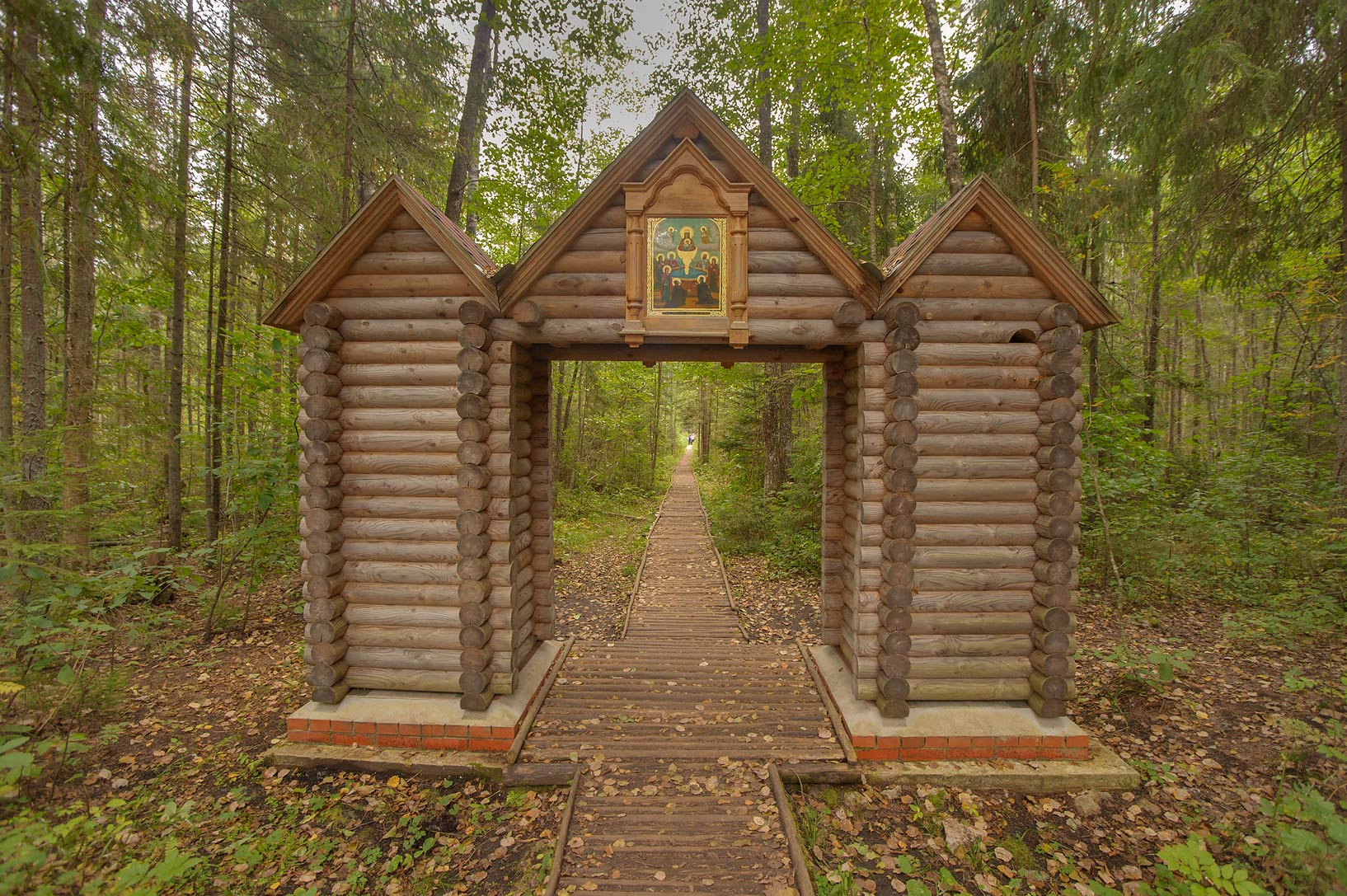 Wooden log gate and boardwalk of sacred radon...Pustyn). Pskov Region, Russia