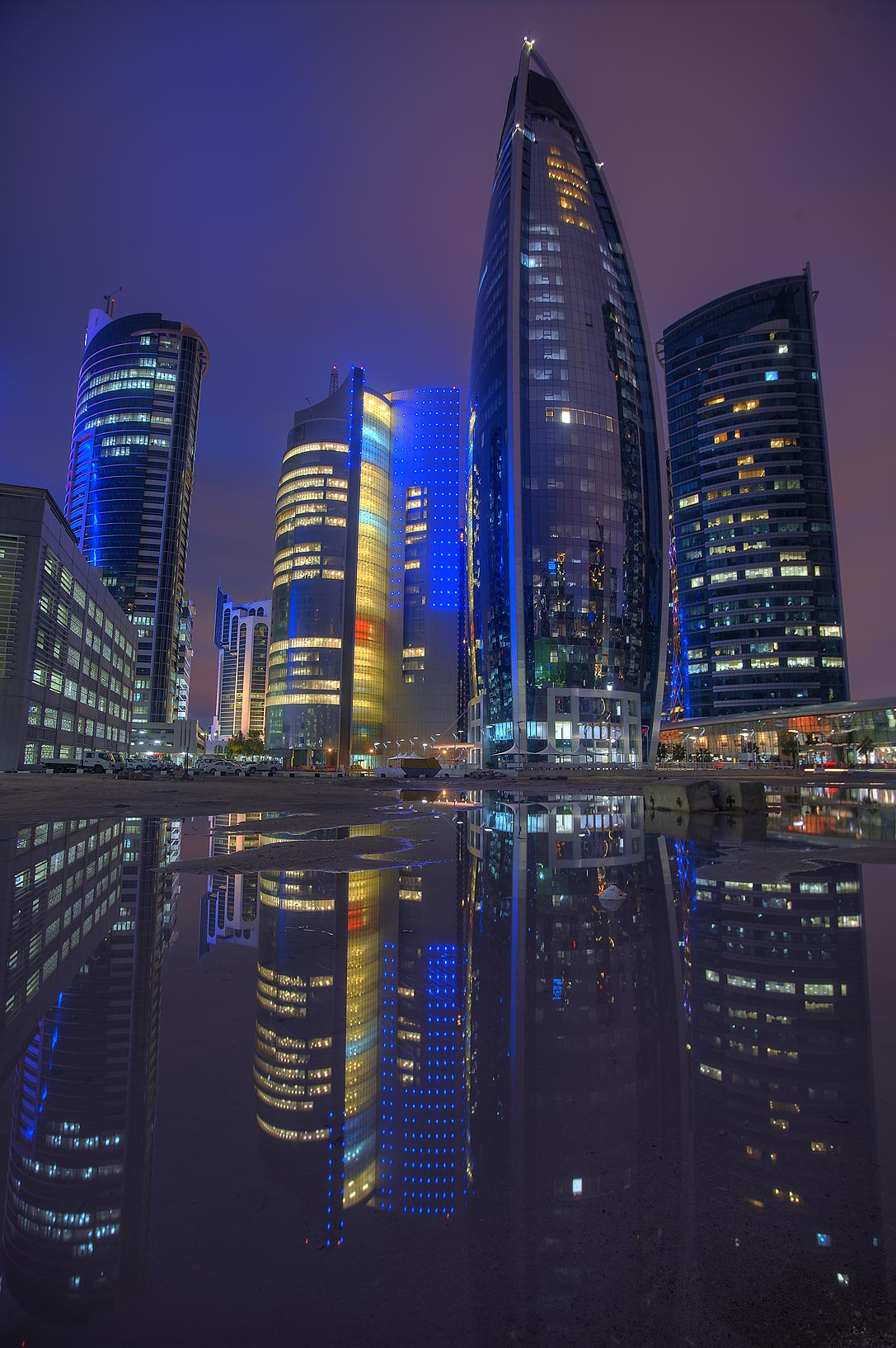 Reflections of Nakheel and Woqod towers in a pool...a parking lot in West Bay. Doha, Qatar