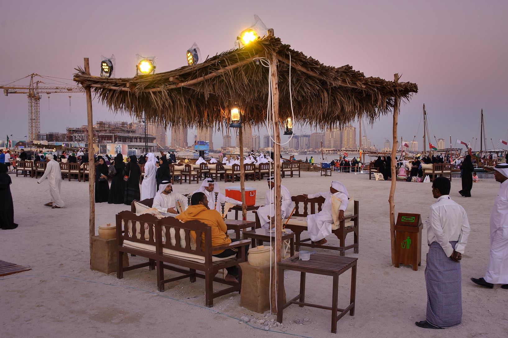 People sitting at Traditional Dhow Festival in Katara Cultural Village. Doha, Qatar