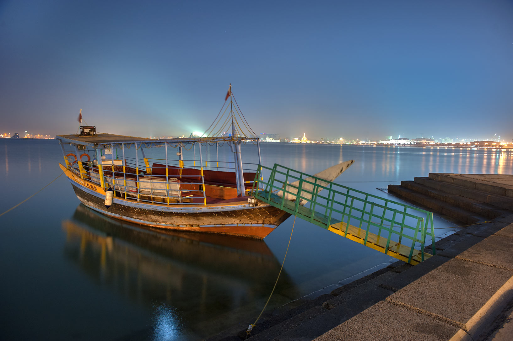 Traditional fishing boat dhow on Corniche promenade. Doha, Qatar