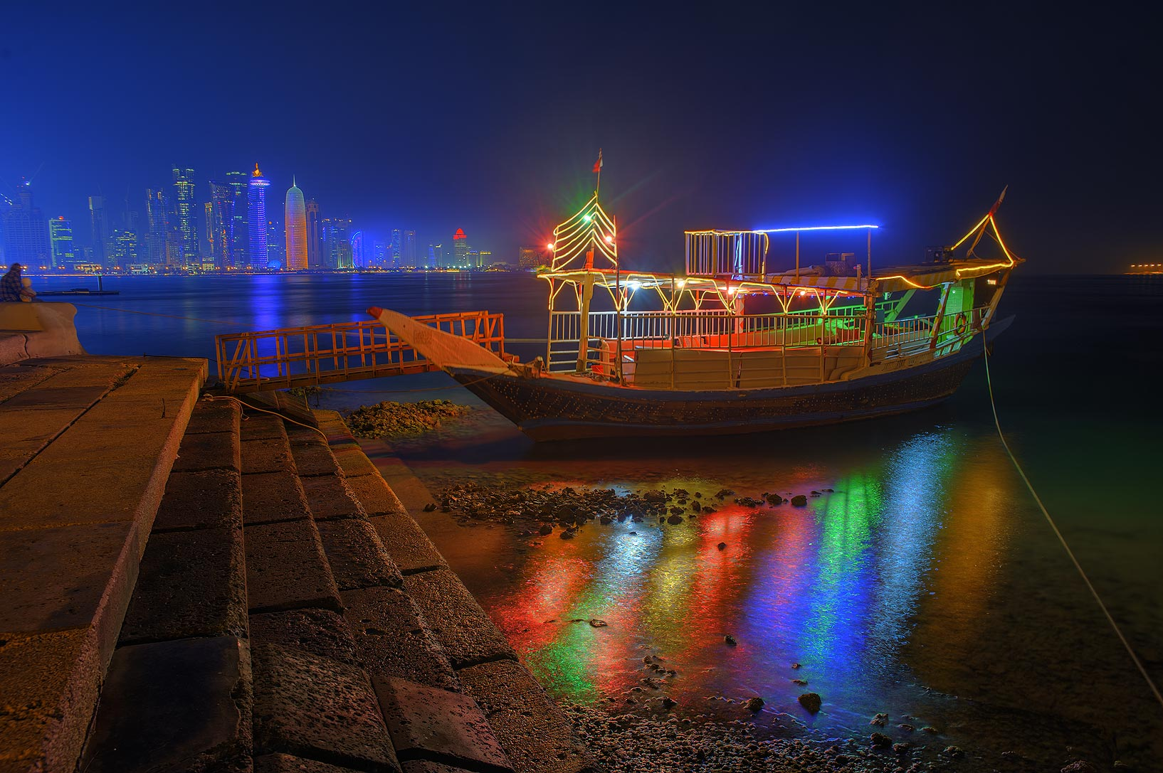 Lights of dhow boat at Corniche promenade at evening. Doha, Qatar