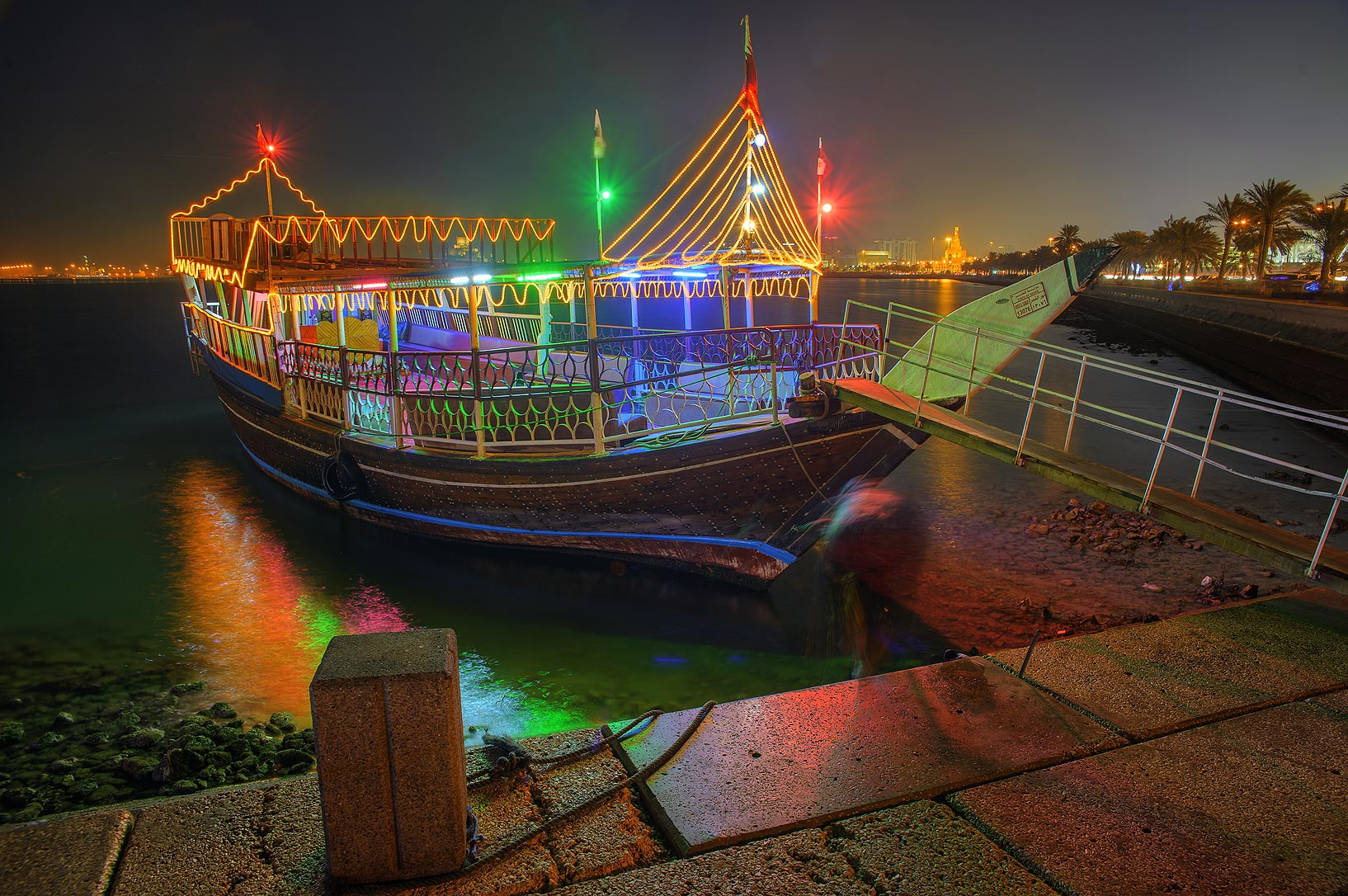 Dhow boat for tourists at Corniche promenade at evening. Doha, Qatar