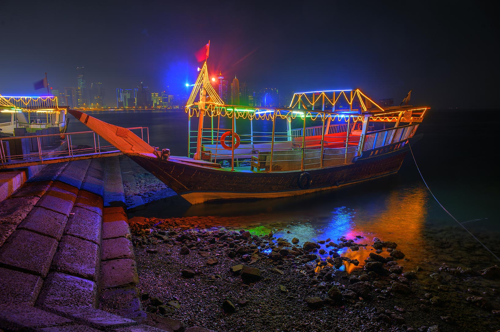 Illuminated dhow boat at Corniche promenade at evening. Doha, Qatar