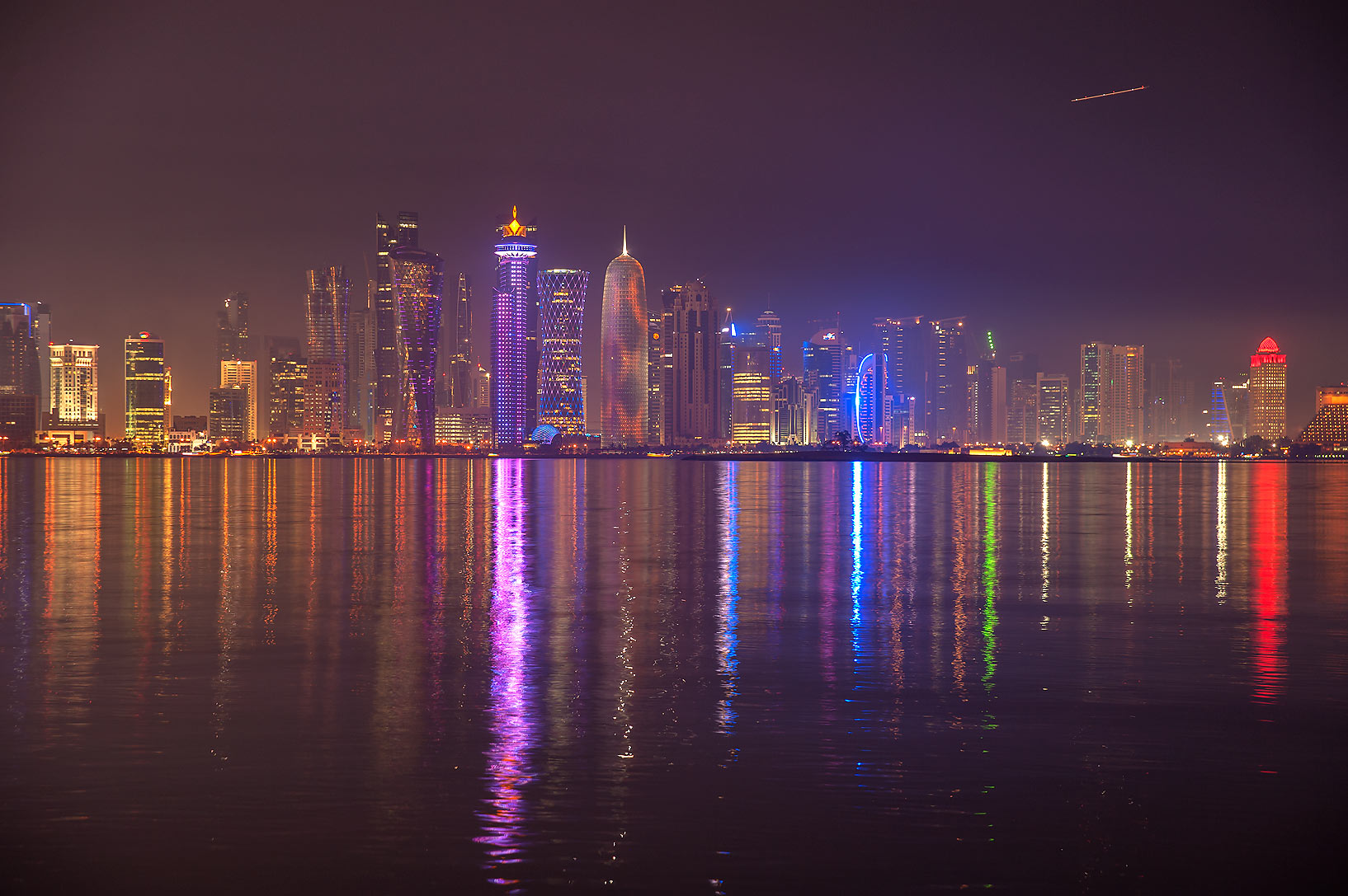 Reflections of West Bay towers from Corniche promenade at evening. Doha, Qatar