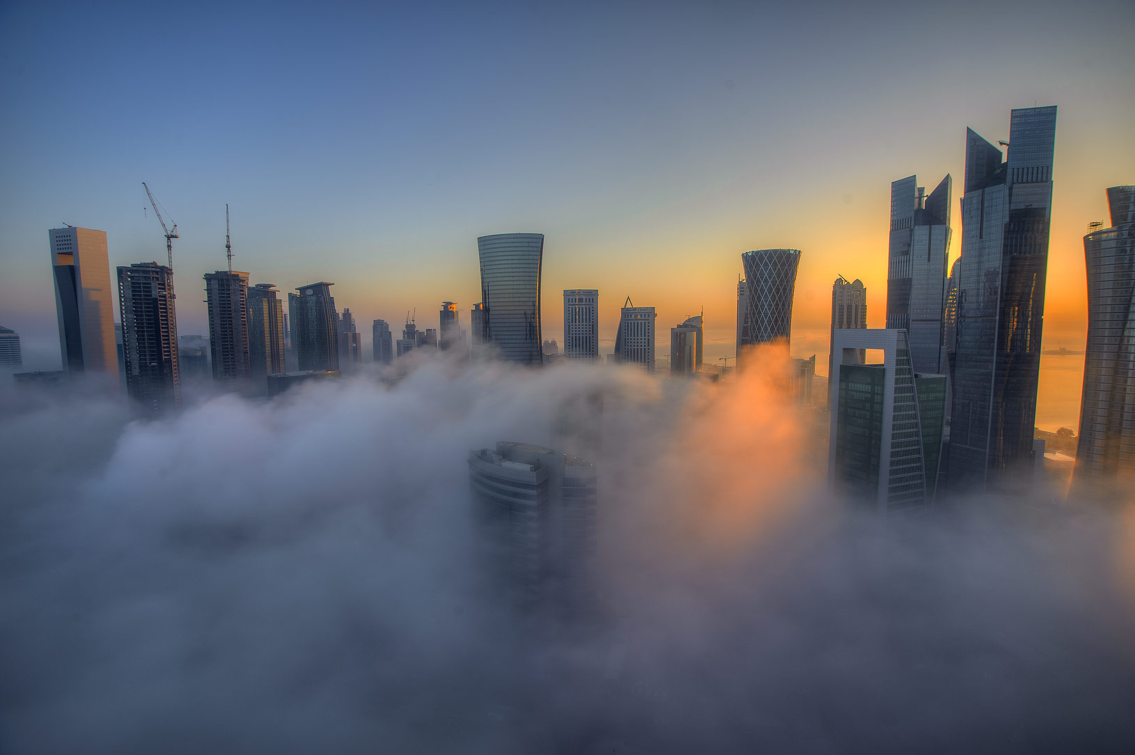 Sunrise through towers in fog to the east from a...Dareen Tower in West Bay. Doha, Qatar