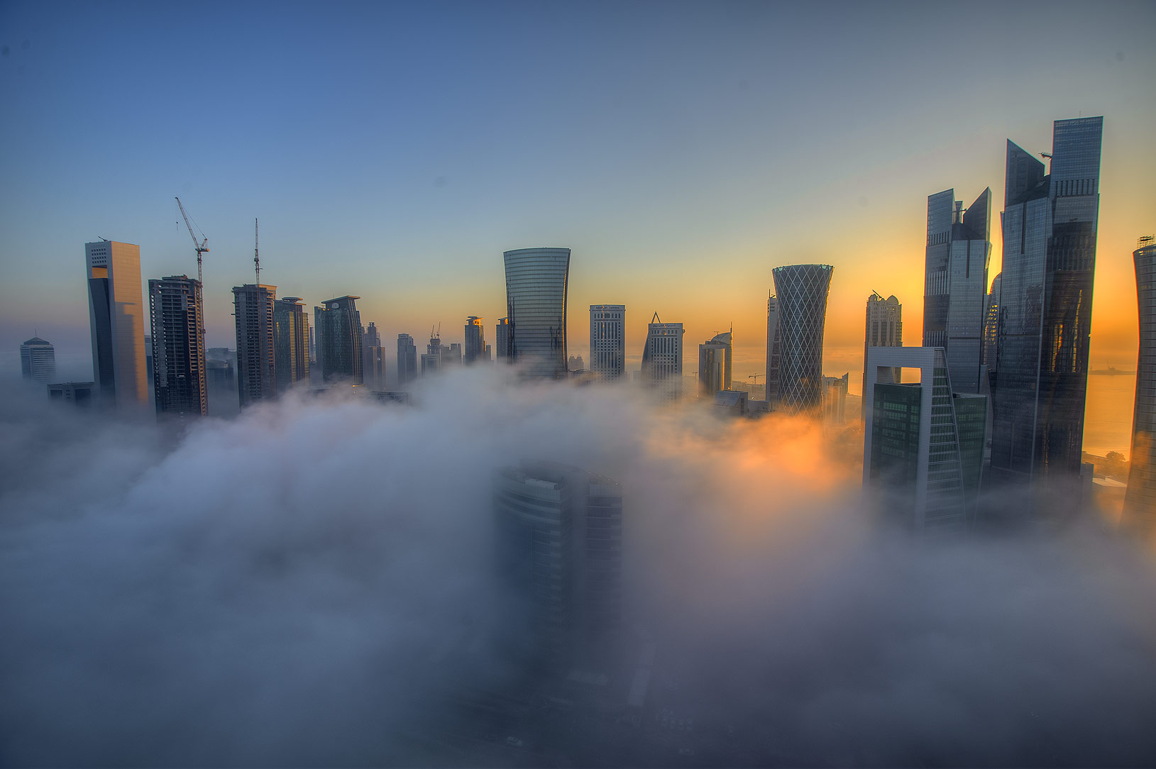 Sunrise through towers in dense fog to the east...Dareen Tower in West Bay. Doha, Qatar
