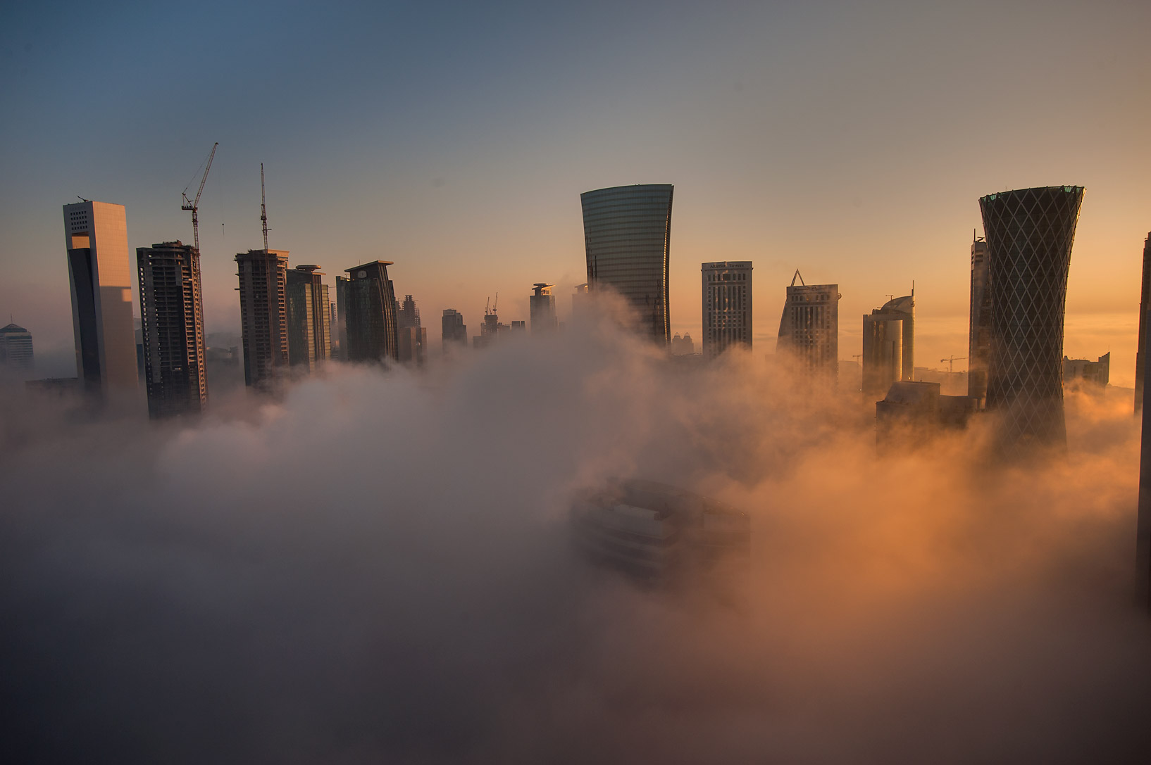 Sunrise through towers in ground fog to the east...Dareen Tower in West Bay. Doha, Qatar