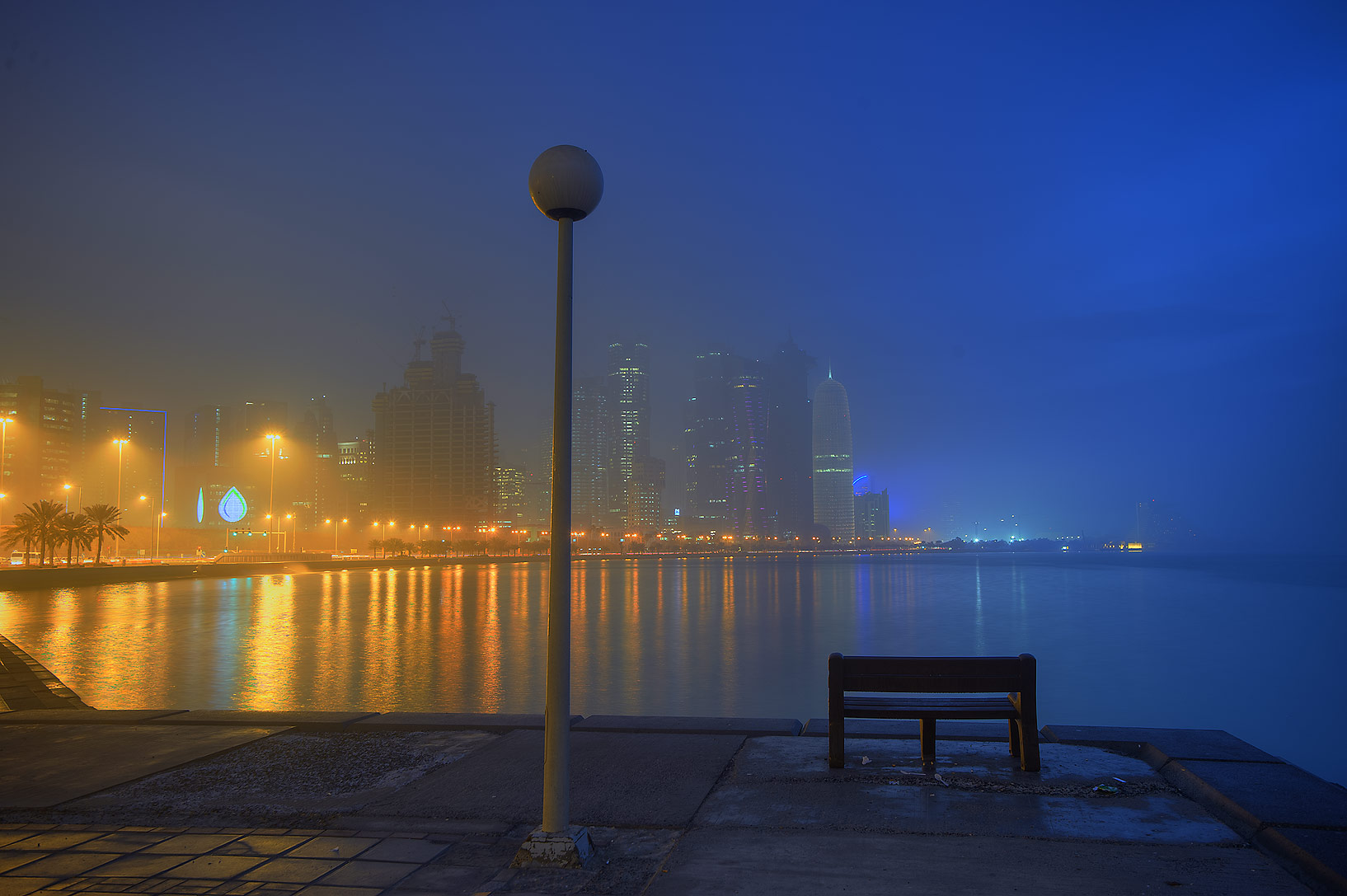 A bench near Balhambar Restaurant and lights of...from Corniche Promenade. Doha, Qatar