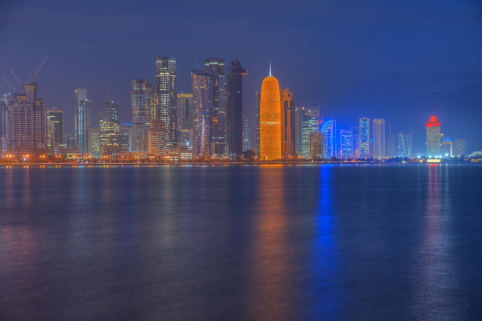 Glowing Burj Qatar Tower in West Bay from Corniche Promenade at morning. Doha, Qatar
