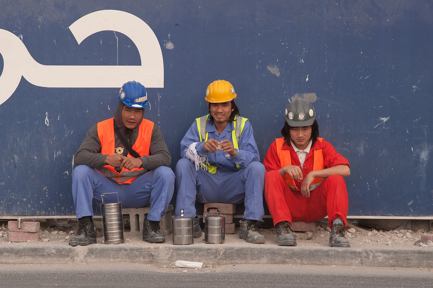 Workers on construction of QP Building sitting...Al Adaid St. in West Bay. Doha, Qatar