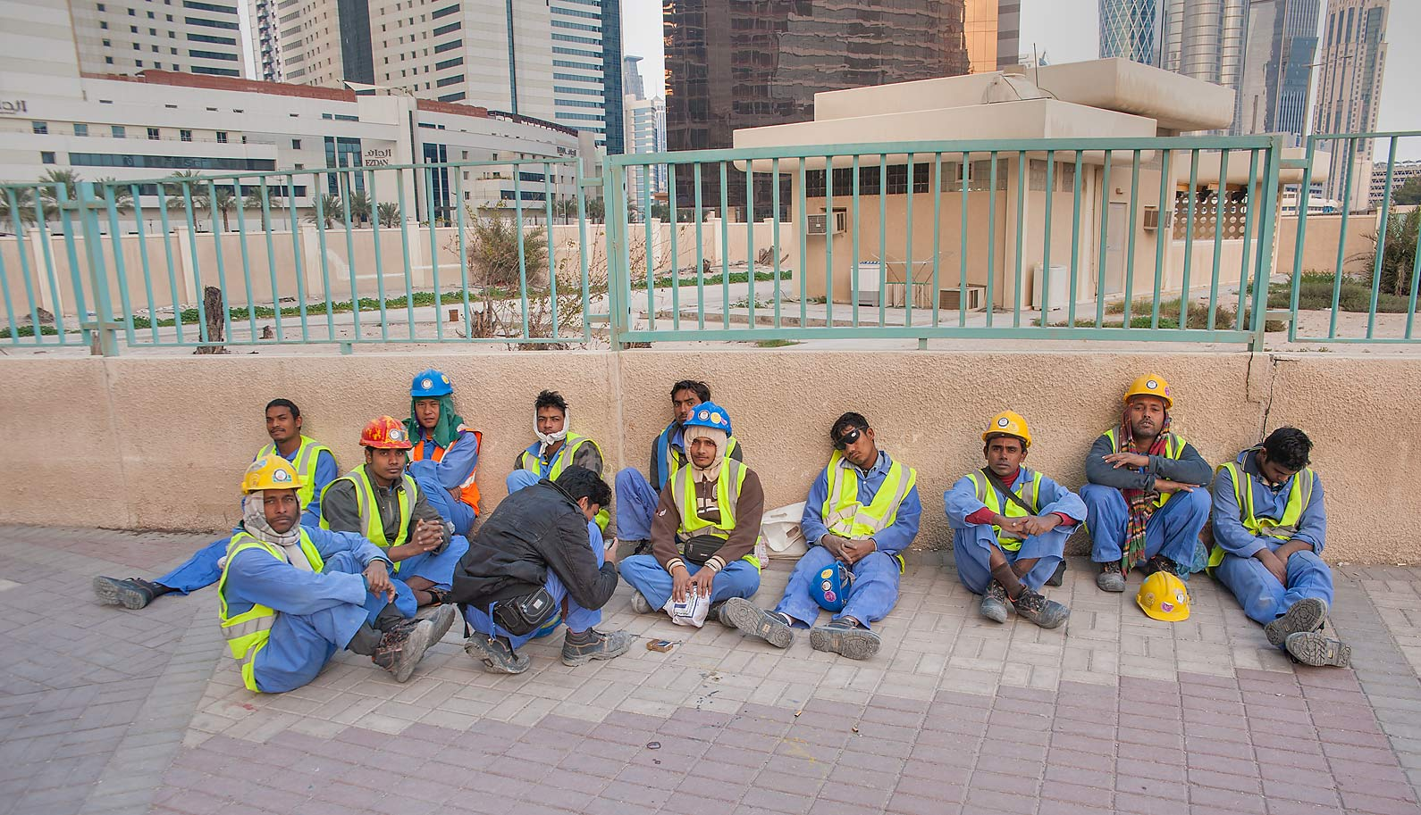 Group of workers on construction of Qatar...Bay sitting after a shift. Doha, Qatar