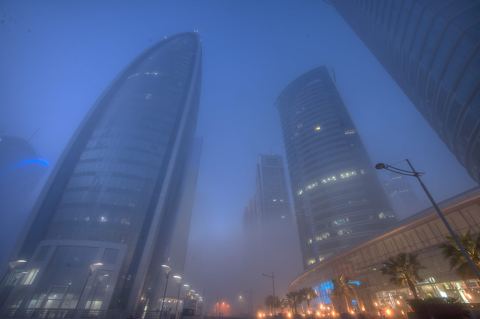 Woqod and Al Fardan towers in West Bay in fog. Doha, Qatar