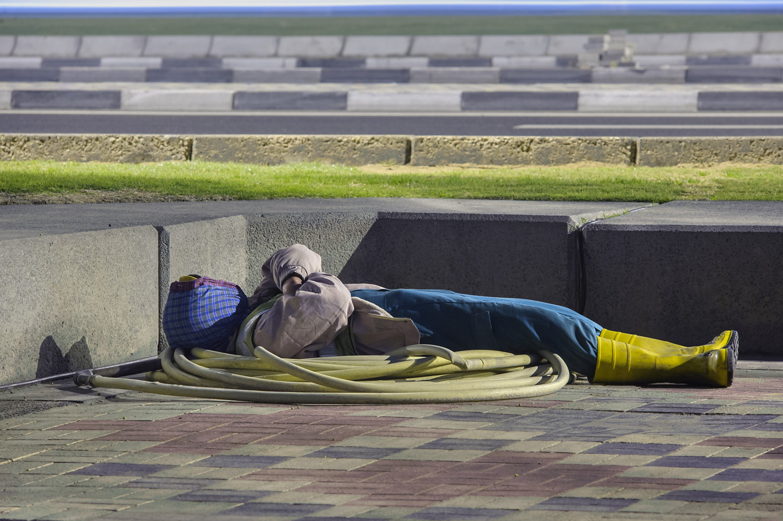 Worker sleeping on water horse on Corniche promenade at morning. Doha, Qatar