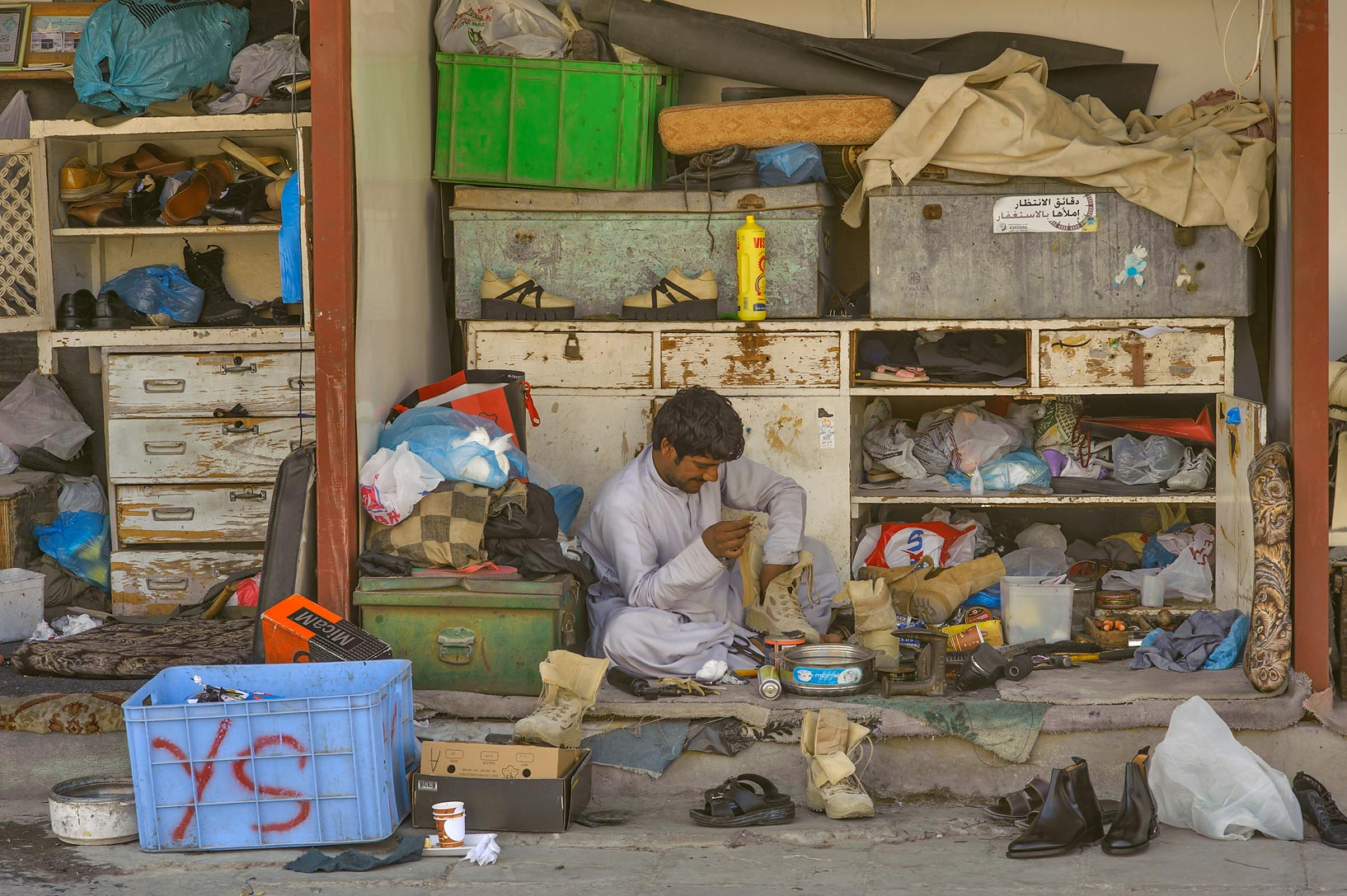 Repairing shoes in Souq Al Ali, near Immigration...Gharafa Interchange). Doha, Qatar