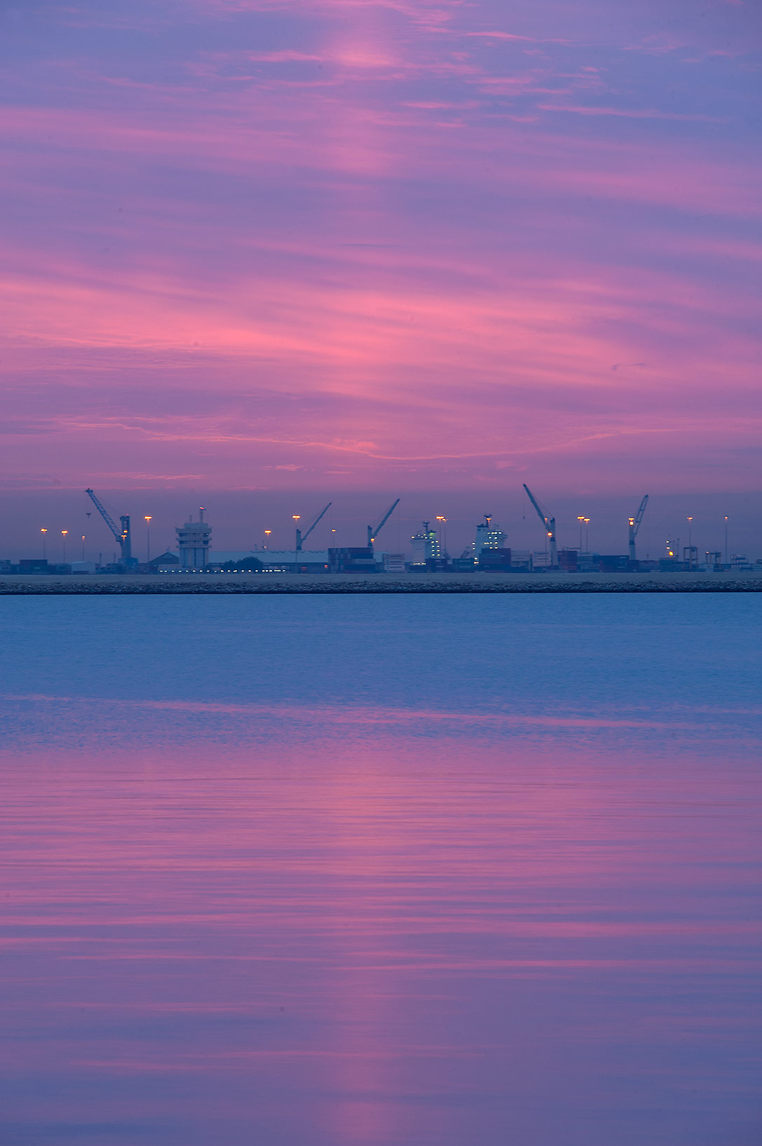 Light pillar at sunrise over Doha port from Corniche promenade. Doha, Qatar