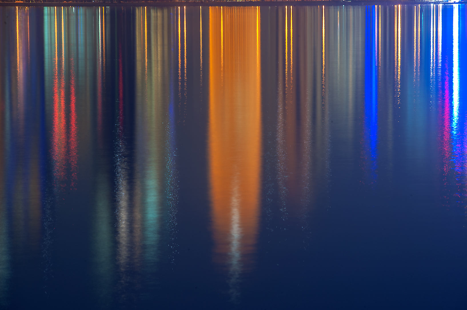 Reflections of lights of West Bay from Corniche promenade. Doha, Qatar