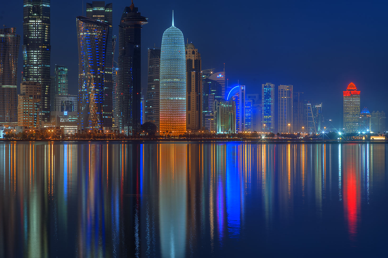 Reflection of lights of West Bay from Corniche promenade. Doha, Qatar