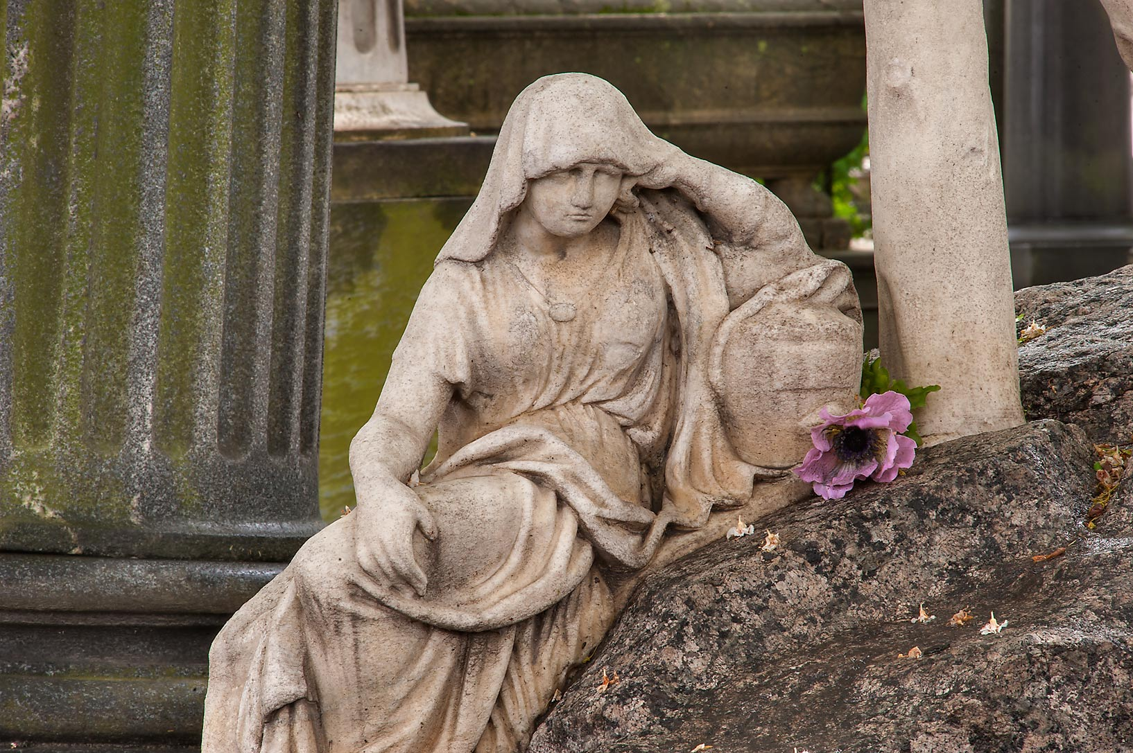 Marble sculpture of a woman sitting on a tomb in...Cemetery). St.Petersburg, Russia