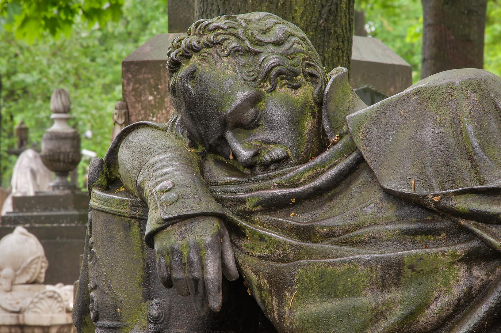 Iron sculpture of a man sleeping on a tomb in...Cemetery). St.Petersburg, Russia