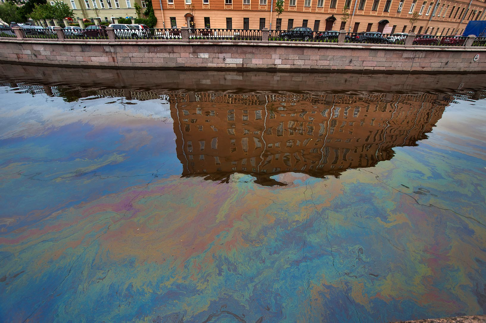 Iridescent oil film on the surface Griboedova Canal. St.Petersburg, Russia