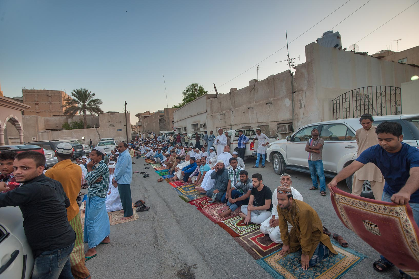 People setting carpets for Eid al-Adha prayer...masjid) in Musheirib area. Doha, Qatar