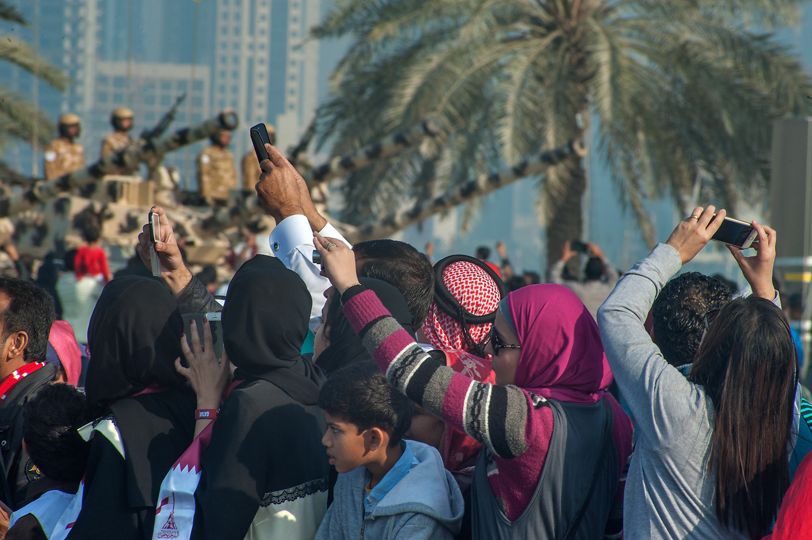 Spectators watching tanks at National Day parade on Corniche. Doha, Qatar