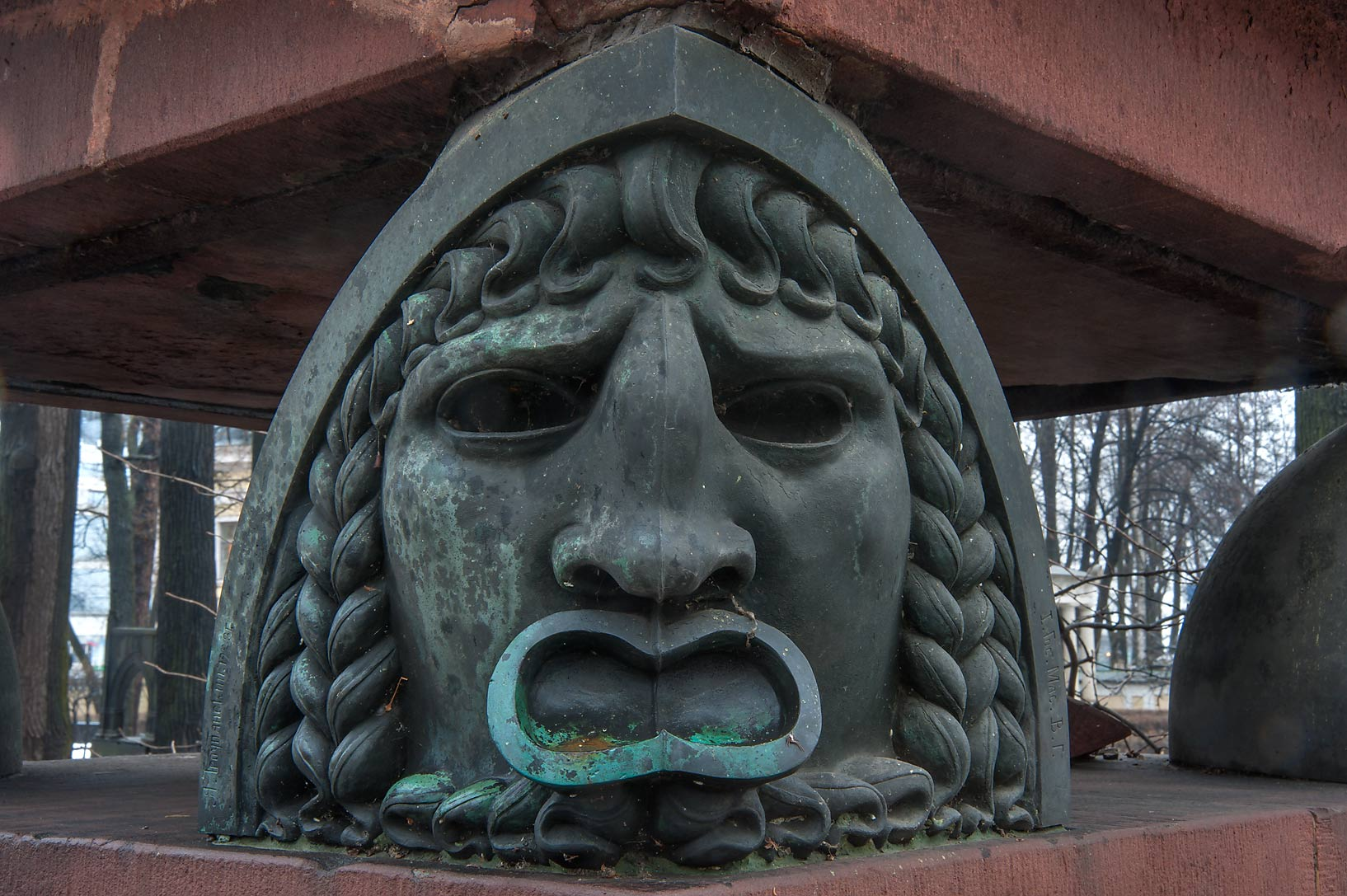 Bronze head supporting tombstone in Necropolis of...Cemetery). St.Petersburg, Russia