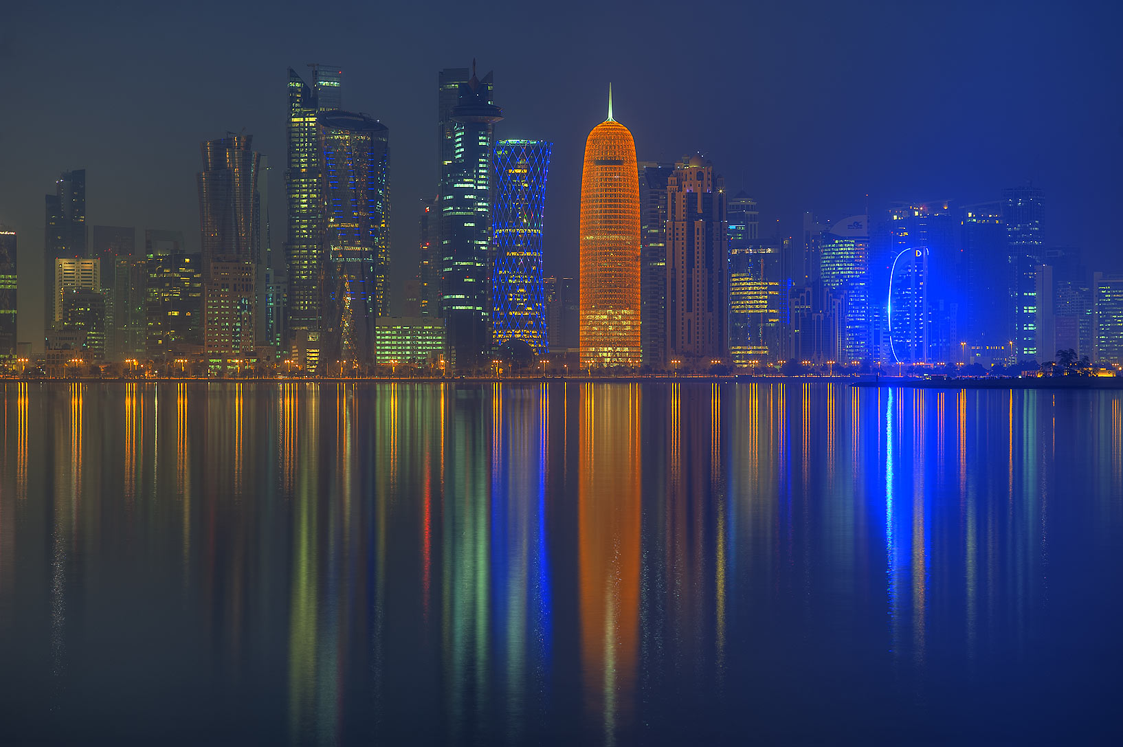 Reflections of lights of West Bay towers from...promenade at morning dusk. Doha, Qatar