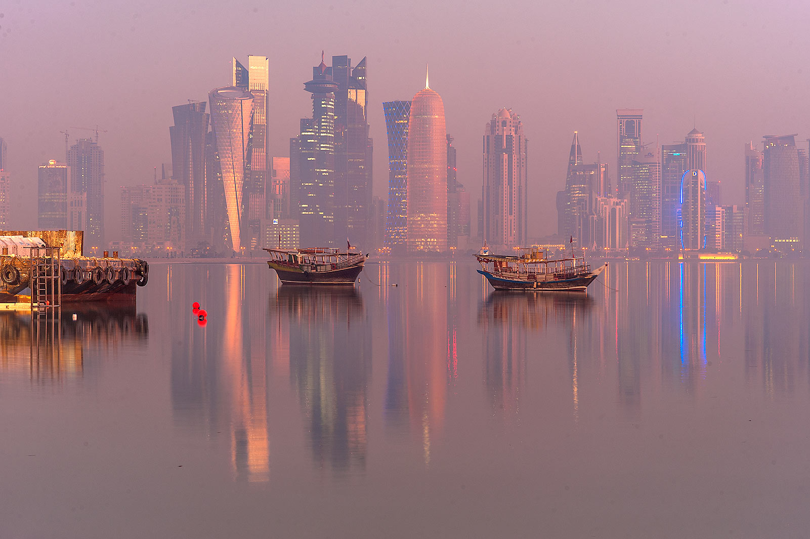 Boats and West Bay towers from Corniche promenade in mist. Doha, Qatar