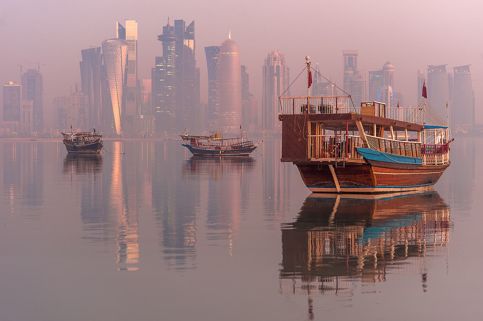 Reflections of dhow fishing boats and West Bay...promenade in mist. Doha, Qatar