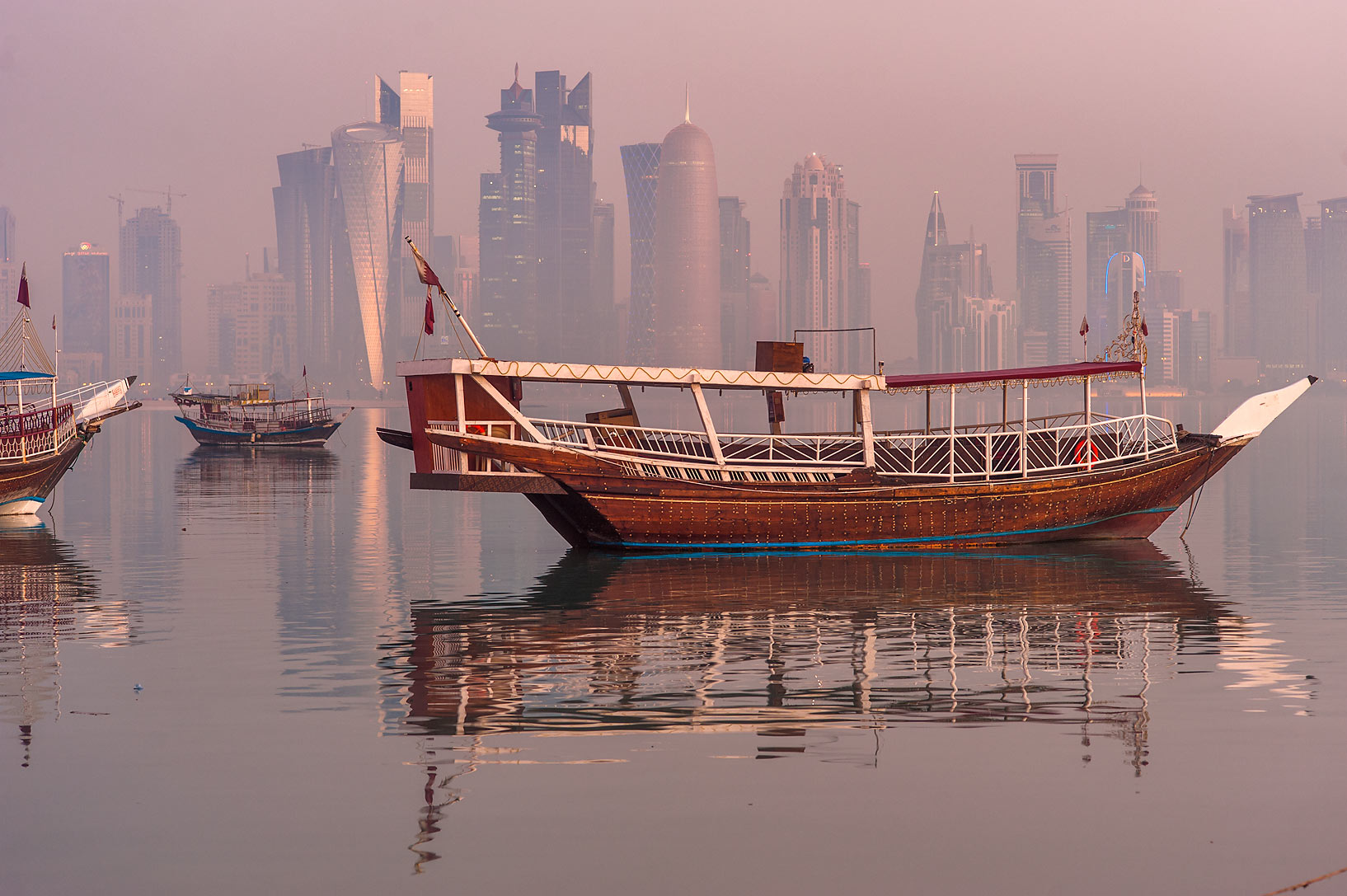 Dhow fishing boats from Corniche promenade in mist. Doha, Qatar
