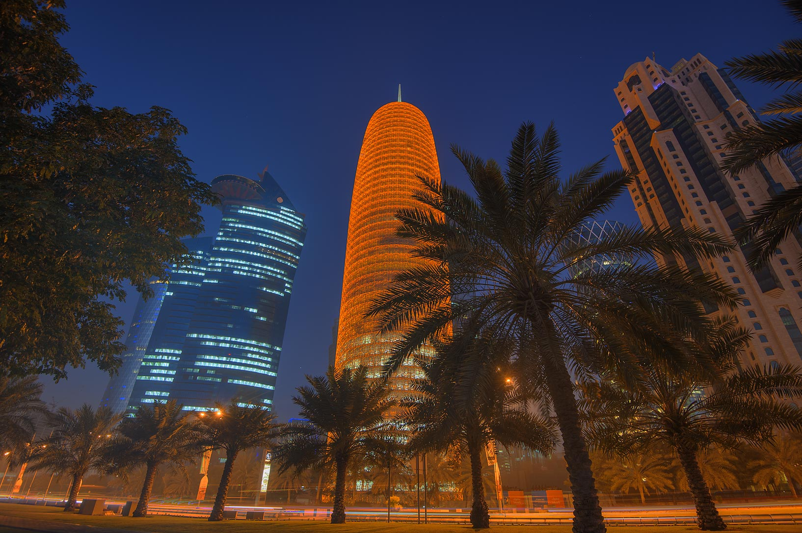 Tornado Tower from a palm alley on Corniche promenade. Doha, Qatar