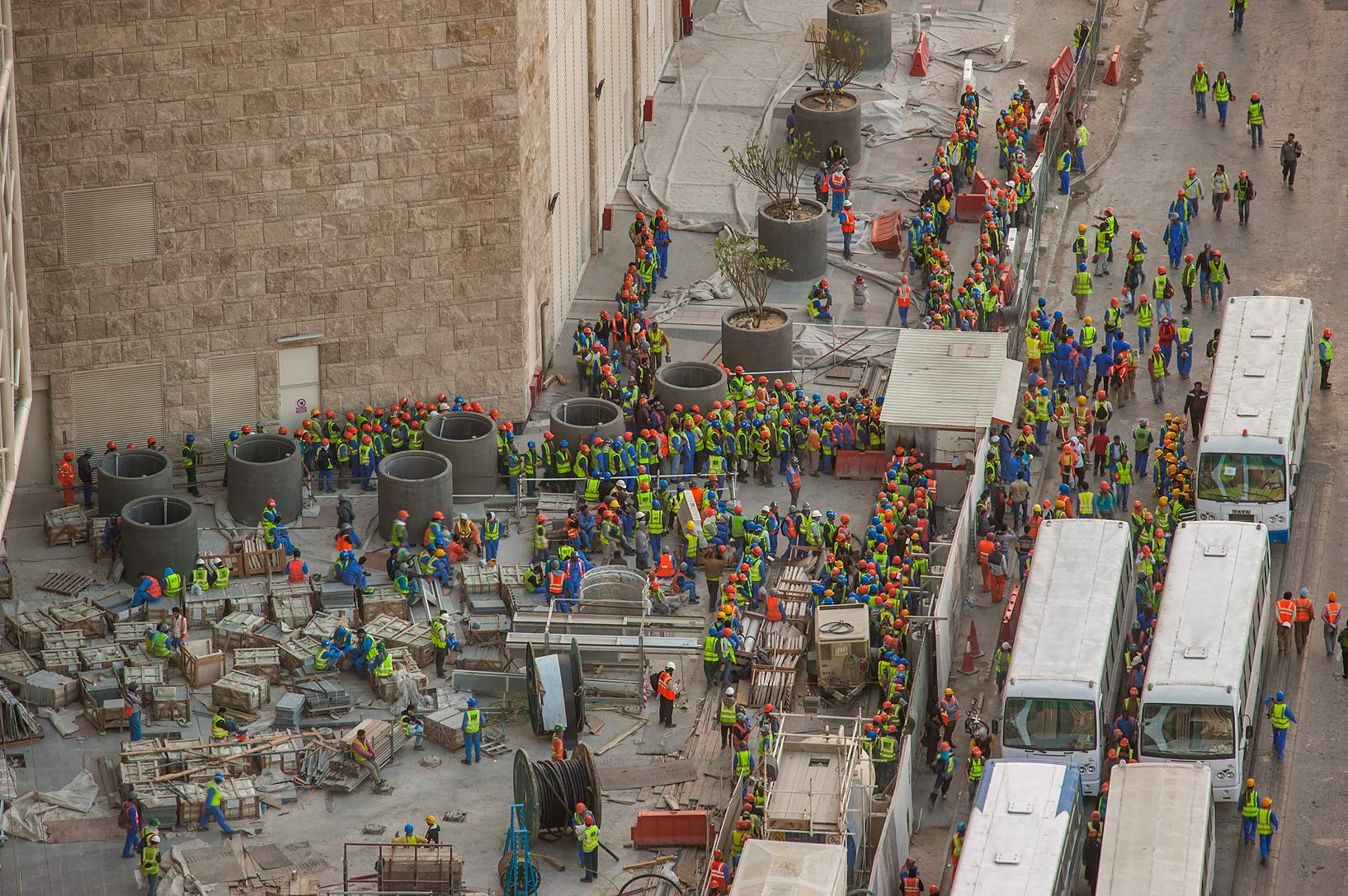 Workers loading buses near construction of Qatar...1-2244 of Ezdan Hotel. Doha, Qatar